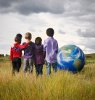 Four Kids of Different Races United Facing a Model of a Globe