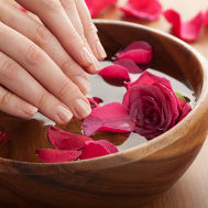 Hands Dipping into Wooden Bowl at Luxurious Spa